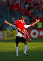 July 21, 2010  Bolton Wanderer Matt Taylor No. 7 is jumped on by Toronto FC Raivis Hscanovics No.34  during the Carlsberg Cup match between the Bolton Wanderers FC and Toronto FC at BMO Field in Toronto..Th Bolton Wanderrs FC won 4-3 on penalty kicks.