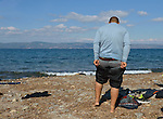 A refugee pulls on dry clothing after crossing the Aegean Sea in a small overcrowded boat from Turkey to Greece, landing on a beach near Molyvos, on the Greek island of Lesbos, on October 29, 2015. The boat was provided by Turkish traffickers to whom the refugees paid huge sums. They were received in Greece by local and international volunteers, then proceeded on their way toward western Europe.