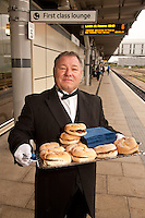 Pictured handing out free bacon butties to promote East Midlands Trains complimentary breakfast for First Class passengers is singing butler Alberto