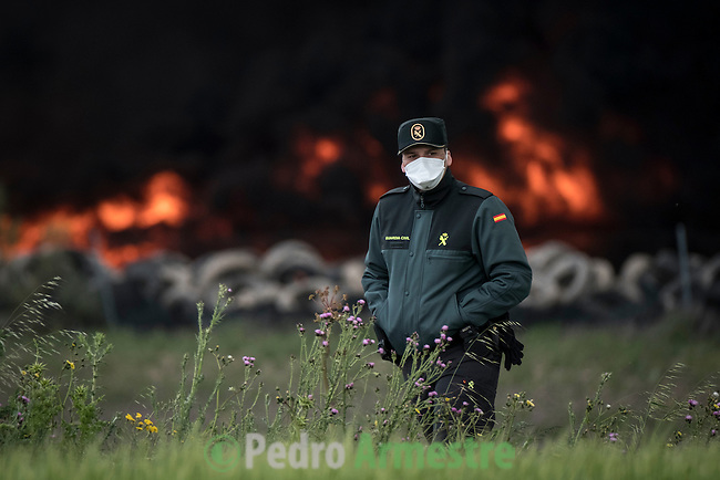 A civil guard with a mask walks past a pile of tyres burning in an uncontrolled dump near the town of Sesena, after a fire broke out early on May 13, 2016. A huge waste ground near Madrid where millions of tyres have been dumped was on fire today, releasing a thick black cloud of toxic fumes that officials worry could harm residents nearby.  © Pedro ARMESTRE