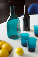 The bottles and glasses seen here on the dining room table are contemporary blue glass