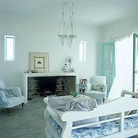 The simple whitewashed living area has an open fireplace and wooden furniture