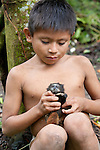 A Machiguenga boy holds a black-mantled tamarin, Manú National Park, Peru.