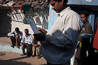 Villagers, all regular subscribers of Khabar Lahariya newspaper, reads this week's issue as it's being distributed by seasoned Khabar Lahariya community journalist Shanti Adivasi, 52, in Manikpur, Chitrakoot, Uttar Pradesh, India on 4th December 2012.  Shanti used to be a wood gatherer, working with her parents since she was 3, and later carrying up to 100 kg of wood walking 12km from the dry jungle hills to her home to repack the wood which sold for 3 rupees per kg. After learning to read and write in an 8 month welfare course, at age 32, she became a reporter, joining Khabar Lahariya newspaper since its establishment in 2002, and making about 9000 rupees per month, supporting her family of 14 as the sole breadwinner. Photo by Suzanne Lee for Marie Claire France.