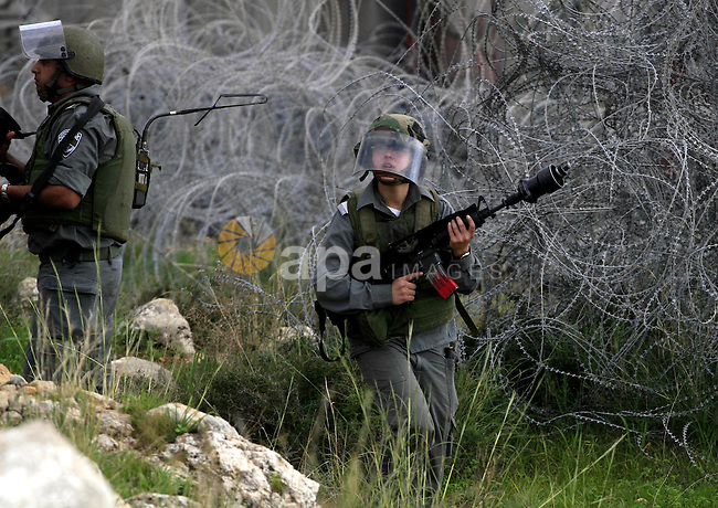 Israeli border police officers take position during a protest by Palestinian and international activists against the controversial Israeli barrier in the West Bank village of Nilin near Ramallah January 1, 2010, to mark the founding of the Fatah movement. Photo by Issam Rimawi