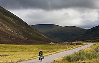 Cyclist on road through the Glen Clunie hills and Grampian Mountains, Scotland, United Kingdom