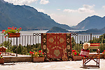 A chair with a straw hat and a red bag sits on a terrace (with a rug on the railing) facing a view of Lake Como, Italy and the town of Bellagio in the background