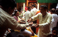 INDIA (West Bengal - Calcutta)  2006, Charanamrita (the water with which the Durga idol is worshiped) is being distributed for drink among the visitors at Mullick family house  (one of the well known families in South Calcutta) on the occassion of Durga Puja Festival. Durga Puja Festival is the biggest festival among bengalies.  As Calcutta is the capital of West Bengal and cultural hub of  the bengali community Durga puja is held with the maximum pomp and vigour. Ritualistic worship, food, drink, new clothes, visiting friends and relatives places and merryment is a part of it. In this festival the hindus worship a ten handed godess riding on a lion armed wth all possible deadly ancient weapons along with her 4 children (Ganesha - God for sucess, Saraswati - Goddess for arts and education, Laxmi - Goddess of wealth and prosperity, Kartikeya - The god of manly hood and beauty). Durga is symbolised as the women power in Indian Mythology.  In Calcutta people from all the religions enjoy these four days of festival in the moth of October. Now the religious festival has become the biggest cultural extravagenza of Calcutta the cultural capital of India. Artistry and craftsmanship can be seen in different sizes and shapes in form of the idol, the interior decor and as well as the pandals erected on the streets, roads and  parks.- Arindam Mukherjee