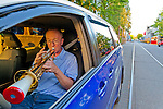 A taxi driver practices his trumpet while waiting for the next fare on Granville Island, British Columbia