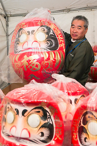 A merchant shows a huge Daruma doll on sale at the Shorinzan Daruma Temple in Takasaki City, Gunma Prefecture on January 6, 2016, Japan. Every year thousands of people visit the country's most famous Daruma market (Daruma ichi) held at the Shorinzan Daruma Temple on January 6 and 7. Takasaki City, is known as the capital of Daruma dolls and about 80% of Japan's Daruma are produced there. According to the tradition, Daruma dolls are sold without pupils painted on their eyes. People color in one pupil when a wish is made or a goal set, and when the wish comes true or the goal is achieved they fill in the other pupil. At the end of the year, used Daruma dolls are returned to the temple to be burned. (Photo by Rodrigo Reyes Marin/AFLO)