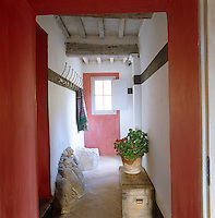 In a corridor of this Tuscan villa red pigments are cleverly used to draw the eye to the window at the far end