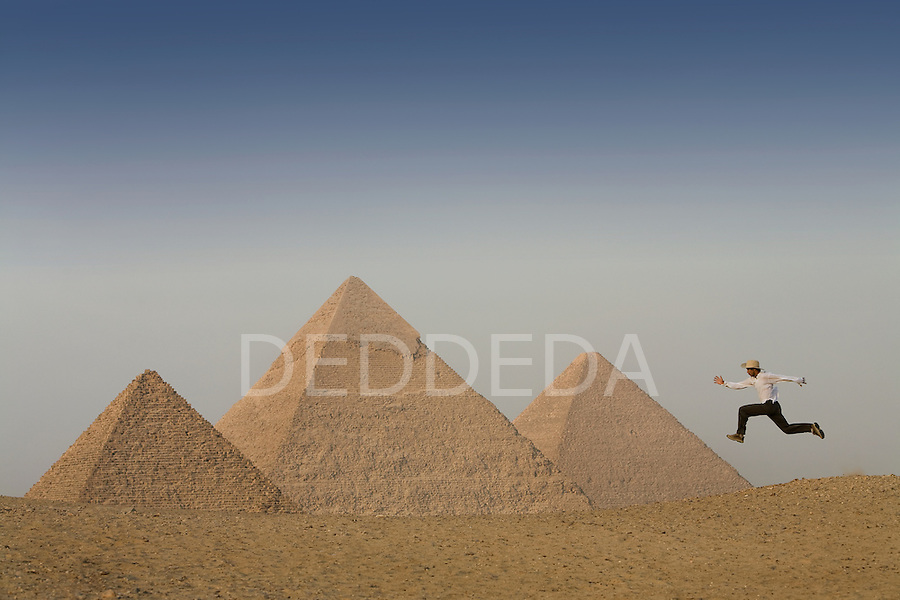 A male tourist wearing a white long sleeved shirt and a hat leaps into the air at the Pyramids of Giza near Cairo, Egypt.
