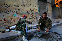 Free Syria Army soldiers clean their weapons after a day of fighting in the al-Amaria district of Aleppo. The man on the right died on September 26 while attempting to move into position for a frontal attack on Syrian forces during urban combat. ..© Javier Manzano.