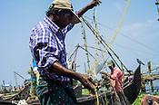 Fisherman untangle their nets on the sea shore in Kochi, Kerala, India.