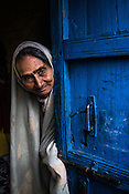An old woman peeps out of the door during a house to house polio drive in Basantpur Sainthly village in Ghaziabad, Uttar Pradesh, India.