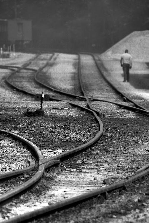 A man walking beside curving railway tracks