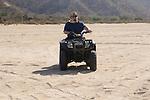 Man riding a Quad in the arroyo near Migrino, Baja California, Mexico