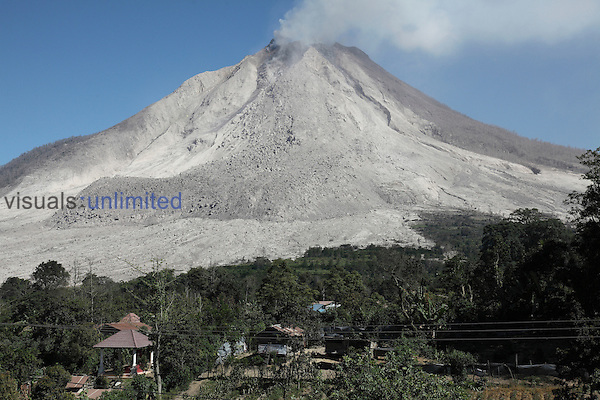 Large andesitic lava flow deposit on flank of Sinabung Volcano, Sumatra, Indonesia with evacuated village in foreground.