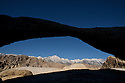 Mt. Whitney and the Sierra Crest appear beneath an unnamed arch in the Alabama Foothills