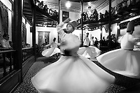Whirling dervishes of the<br /> Mevlana Order presenting Sama, a formal religious ceremony aiming to achieve ecstacy, at the Mevlana cultural centre, Bursa, Turkey. This Sufi order was founded in Konya (then capital of the Anatolian Seljuk Sultanate) by the followers of Rumi, a 13th-century Persian poet. They are known as the Whirling Dervishes due to their famous practice of whirling as a form of dhikr (remembrance of God). Picture by Manuel Cohen