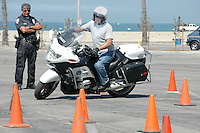 Santa Monica Police Officer Scott Pace, maneuvers his way through a cone pattern coarse at the Santa Monica Beach, testing his skills before the watchful eyes of SMPD Motor Officer David Enriquez, who coaches him along on Tuesday, June 7, 2011. Pace is practicing for an upcoming motorcycle training school.