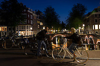 Cyclists by illuminated bridges at Kaisersgracht and Leidsegracht, canal ring area, Jordaan district, Amsterdam