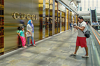 A tourist photographs his companions as they pose beside the logo of a Gucci outlet in the shopping mall at the Marina Bay Sands resort hotel.