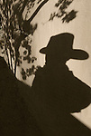 The shadow of a man wearing a cowboy hat and a tree on a wall