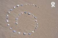 Pebbles arranged in spiral shape on beach (Licence this image exclusively with Getty: http://www.gettyimages.com/detail/83676018 )