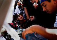 Tecate, Baja California, MX, Oct. 14, 2007 - Octavio Ramon, 12, lower left, cries along with his grandmother, Beatrice, and cousin Hector, at the coffin of his grandfather, Raul, who was killed by drug dealers on his way home from work. The U.S. Border Patrol says that Tijuana is the largest entry point for drug smuggling into the U.S. As they have struggled to get this under control, the smugglers are looking for new entry points, such as in Tecate and beyond.