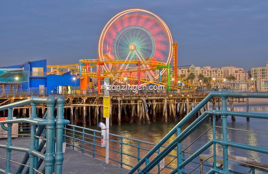 Santa Monica CA Pacific Pier Ferris Wheel moving near sunset, family amusement park large New Pacific Ferris wheel Roller Coaster moving over the ocean
