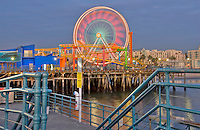 Santa Monica CA Pacific Pier Ferris Wheel moving near sunset, family amusement park large New Pacific Ferris wheel Roller Coaster moving over the ocean