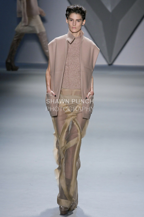 Marie Piovesan walks runway in a nude melton oversized sleeveless cape with stand collar over nude wool boucle fencing vest and silk chiffon cotton net tank, and nude silk chiffon crisscross appliqué cotton net floor-length skirt with organza flange detail over nude silk chiffon boy short, from the Vera Wang Fall 2012 Vis-a-gris collection, during Mercedes-Benz Fashion Week Fall 2012 in New York.