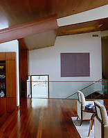 The matching mahogany of the floor boards and ceiling cladding create a sense of harmony in this open-plan living space