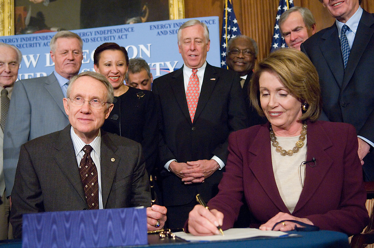 WASHINGTON, DC - Dec. 18: Backed by Senate and House members, Senate Majority Leader Harry Reid, D-Nev., and House Speaker Nancy Pelosi, D-Calif., signing, during an enrollment ceremony for the energy bill, passed by the House earlier Tuesday. Left to right: House Foreign Affairs Chairman Tom Lantos, D-Calif., House Education Chairman George Miller, D-Calif., House Agriculture Chairman Colin C. Peterson, D-Minn., Rep. Nydia M. Velazquez, D-N.Y., House Democratic Caucus Chairman Rahm Emanuel, D-Ill., House Majority Leader Steny Hoyer, D-Md., House Majority Whip James E. Clyburn, D-S.C., Senate Energy Chairman Jeff Bingaman, D-N.M., and House Select Energy Independence & Global Warming Chairman Edward J. Markey, D-Mass. They sent President Bush a streamlined energy bill that would make the first statutory increase in fuel economy standards in 32 years and require billions more gallons of biofuels to be blended into gasoline over the next 15 years. The president plans to sign the legislation Wednesday, White House spokeswoman Dana Perino said. The bill passed the House by 314-100. (Photo by Scott J. Ferrell/Congressional Quarterly).