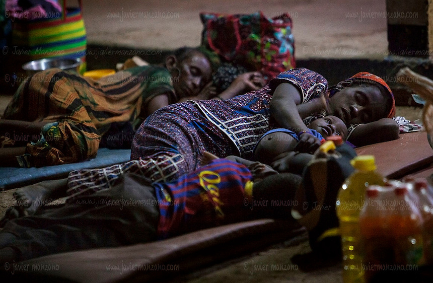 AGADEZ, NIGER &mdash; <br /> A mother sleeps on the ground of the Agadez bus station along her two sons. Dozens of poor migrants regularly sleep on the streets as they continue their journey north - with police and military checkpoints throughout each country they prefer to travel with little money to prevent these security forces from taking it away from them. Most smugglers are paid in advance through Western Union, a popular money transfer banking system.