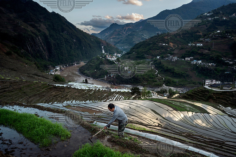 Qian Yi Qiu, 40, a Lisu villager works in his rice terraces which overlook the Nujiang River in Lawu Village.