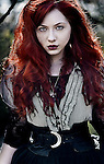A close up of a girl with red hair wearing Victorian garments
