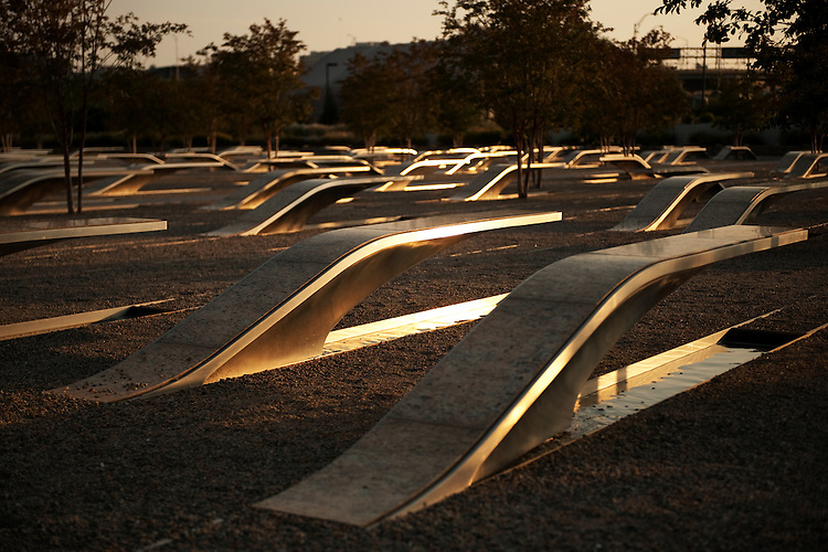 UNITED STATES - SEPTEMBER 01:  The setting sun reflects off benches at the Pentagon Memorial, outside of the Pentagon in Arlington Va.  Each bench is dedicated to one of the 184 people that died on 9/11/01 in the Pentagon and American Airlines Flight 77. (Photo By Tom Williams/Roll Call)
