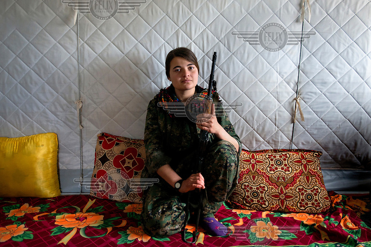 A portrait of Dersim, a 21 year old Yazidi refugee from Sinjar. Dersim, who once wanted to become a beautician, is now a member of YBJ, a female Yazidi battalion of the Sinjar Resistance forces (YPG) which is trained by Kurdistan Worker's Party (PKK) fighters from Turkey, Syria and Iran. 'One month after I started working at a local beauty parlour in Sinjar, Islamic State (IS) attacked us. I was running to the mountain and was hoping that Peshmerga and Kurdish fighters would protect us but they ran away too and it was only PKK fighters who protected and supported us. When I saw women from Syria who were fighting for us in August (2014) I thought I also wanted to be like them and protect ourselves in future. I don't want to get married, I don't need children and I'm even ready to die for Sinjar.' Dersim says. <br /> Thousands of Yazidis fled to the mountains when Islamic State (IS) fighters attacked towns and villages around Sinjar in August 2014. Since then Yazidi refugees have been living in precarious conditions with no electricity or running water and children haven't been attending school. Support from the international community has been insufficient and people are dying of hunger and disease. Until December 2014 the mountains were surrounded by IS. Now the southern part of the mountains is still under IS control.