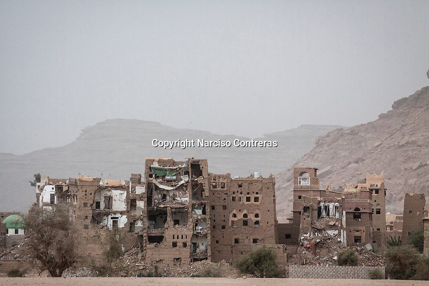"""Wednesday 15 July, 2015: Residential house buildings partially destroyed by heavy fighting are seen in the outskirts of Sa'dah, a city subdued to heavy bombardments carried out by the Arab states and their western allies led by Saudi Arabia in the northern province of Sa'dah, the stronghold of the Houthi's movement declared unilaterally """"a military zone"""". The historic city of Sa'dah is among the places submitted on a tentative list to be under protection of UNESCO as a World Heritage site like the others enlisted cultural heritage sites in Yemen, such as the historic town of Zabid, the Old City of Sana'a and the Old Walled City of Shibam endangered by the ongoing aerial campaign of bombardments. (Photo/Narciso Contreras)"""