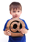 Two year old boy holding AT email symbol in his hands isolated on white background