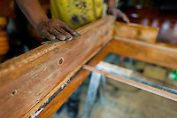 A carpentry worker polishes the wooden case with a fine sandpaper at a table football workshop in Quito, Ecuador, 3 March 2012. Table football, also known as futbolin in Latin America, is a widely popular table-top game in Ecuador. During the annual fairs, the rusty old outdoor-designed tables, fully ocuppied by excited children, may be found on all public places, particularly on the squares and in the parks. Although there have always been several small table football workshops in all large Ecuadorean towns, the table football craft and tradition is on a decline in last years, mainly due to the video-game boom.