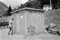 "Switzerland. Canton Ticino. Maggia valley. Cevio. A man working for Cevio's village opens the door of a small building intended for electricity purpose. A heart is painted on the wall with the words ""Tourist""and "" Hyper"". 12.05.2015 © 2015 Didier Ruef"