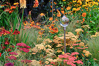 Achilea, Helenium, Kniphofia, Dahlia, ornamental grass, glass garden ornament for sunset hot warm toned color theme garden of orange, yellow, reds perennials flowers