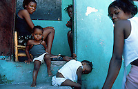 Haiti. Province of Ouest.  Port-Au-Prince.  Slum of Campeche. Densely populated area. Daily life for young people who are jobless. They have nothing to do. The women take care of their young children .  © 2003 Didier Ruef