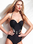 Beautiful young woman wearing a fashionable one-piece monokini swimsuit isolated on white wall background