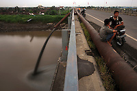 Mud is released by pipe into the Porong River at the bridge near Besuki village. Since May 2006, more than 10,000 people in the Porong subdistrict of Sidoarjo have been displaced by hot mud flowing from a natural gas well that was being drilled by the oil company Lapindo Brantas. The torrent of mud - up to 125,000 cubic metres per day - continued to flow three years later.