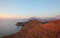 View of the coast from the Mirador de la Amatista, with the double peak of the Pico de los Frailes volcano in the distance, at 500m the highest mountain in the  Sierra de Cabo de Gata, in the desert landscape of the Cabo de Gata-Nijar Natural Park, Almeria, Andalusia, Southern Spain. The park includes the Sierra del Cabo de Gata mountain range, volcanic rock landscapes, islands, coastline and coral reefs and has the only warm desert climate in Europe. The park was listed as a UNESCO Biosphere Reserve in 1997 and a Specially Protected Area of Mediterranean Importance in 2001. Picture by Manuel Cohen