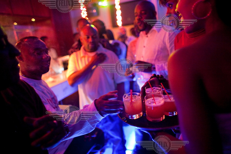 Men reach for drinks at the upscale nightclub Saipan, frequented by hip hop stars, and other wealthy Nigerians.